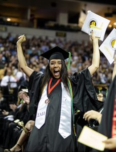 A woman in cap and gown raising her hands in celebration after receiving her diploma at the UCF Arena